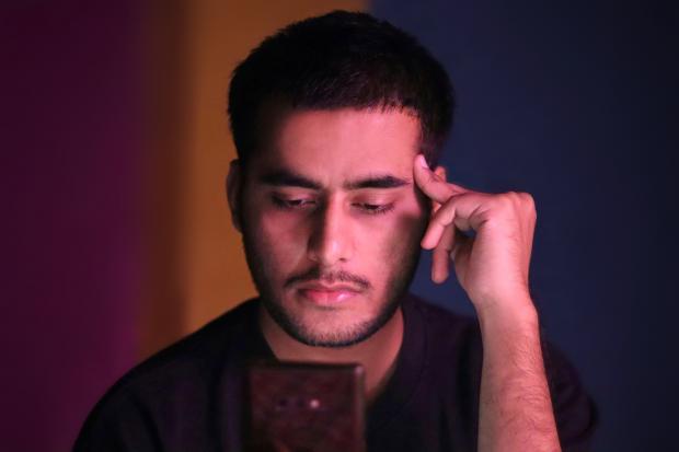 молодой мужчина держит палец у виска