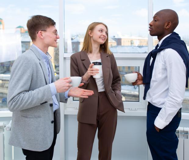 два парня и девушка пьют кофе и общаются