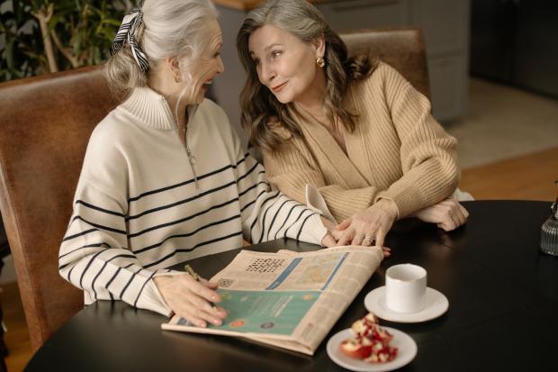 две пожилые женщина разгадывают кроссворд в газете