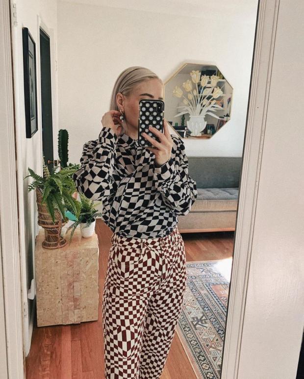 девушка в брюках и блузке а-ля шахматная доска делает селфи