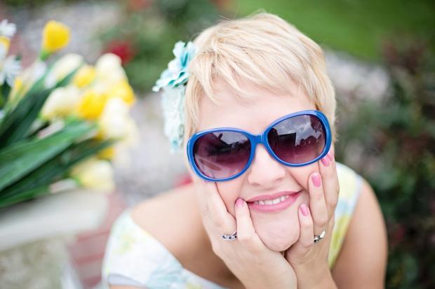 блондинка улыбается с короткой стрижкой и в солнцезащитных очках
