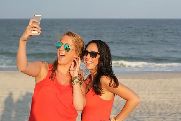 девушки в красных сарафанах и очках делают селфи на пляже