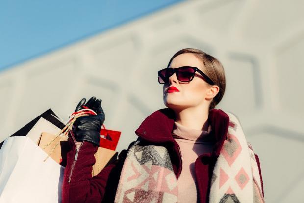 девушка возвращается из магазина в очках от солнца