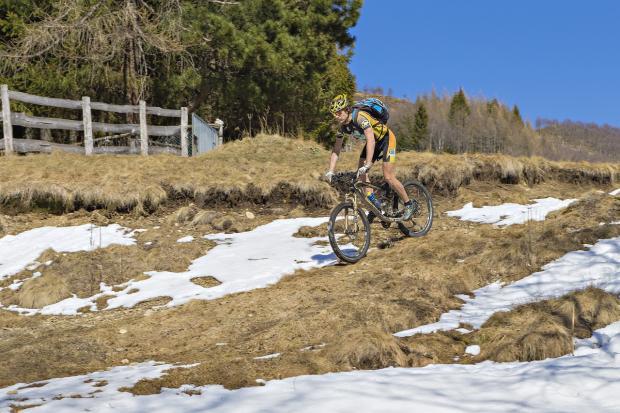мужчина спускается по пригорку на велосипеде весной