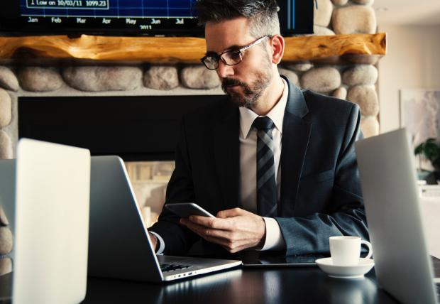 мужчина в очках с телефоном в руке работает на ноутбуке