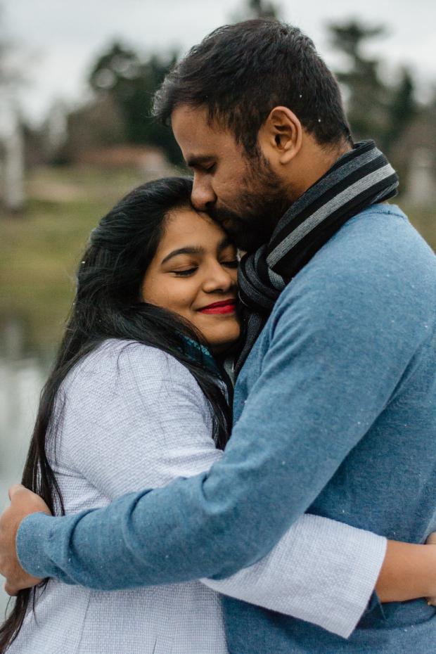 мужчина в голубом джемпере обнимает девушку