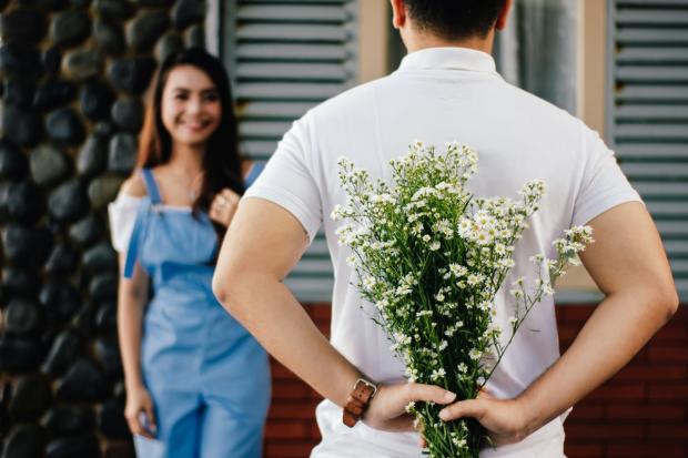 мужчина в белой футболке держит за спиной букет ромашек