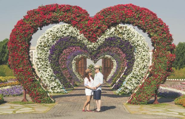пара стоит на фоне цветов в виде сердца