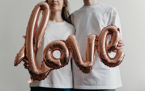 мужчина с девушкой в белых футболках держат в руках слово Любовь