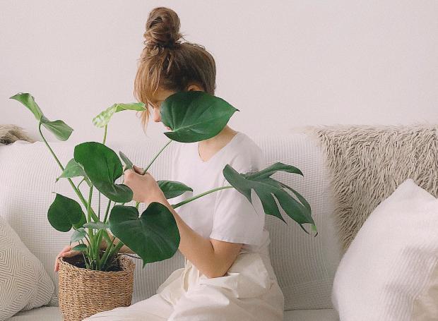 девушка в белой футболке с домашним цветком
