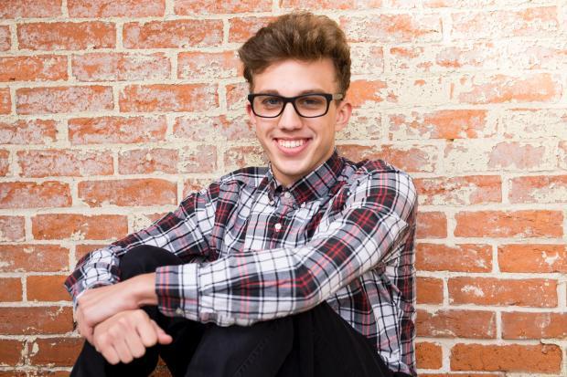 молодой мужчина в клетчатой рубашке и очках