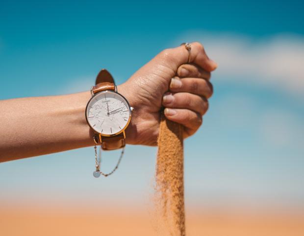 рука с часами сыпет песок