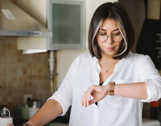 молодая женщина в белой блузе смотрит на часы на руке