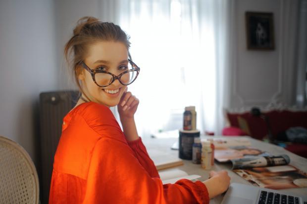 молодая девушка в очках и оранжевой блузе