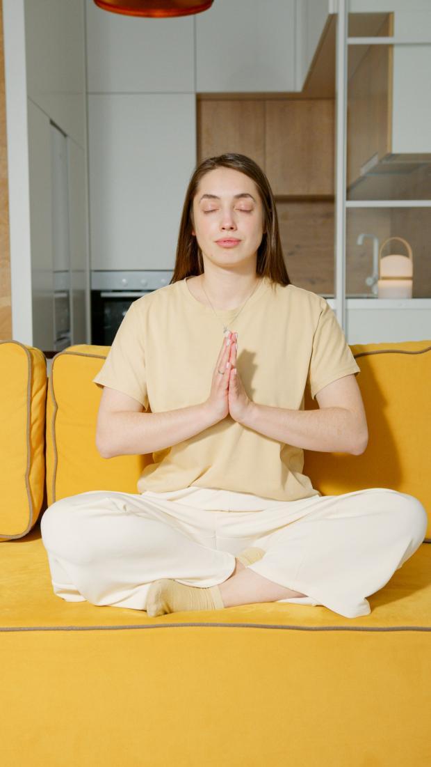 девушка медитирует дома на желтом диване
