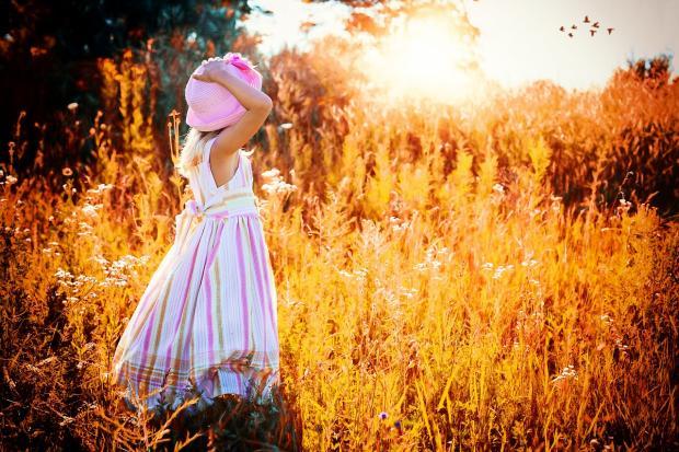 девочка в белом сарафане и розовой шляпке смотрит на закат