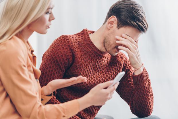 Женщина с телефоном руках и мужчина в бордовом свитере