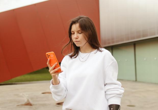 молодая девушка в белом худи держит в руках мобильный телефон