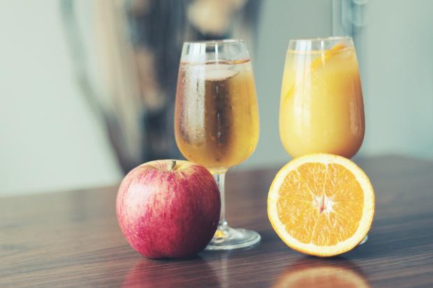 яблоко, половинка апельсина, яблочный и апельсиновый сок