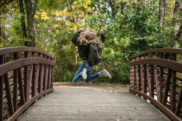 девушка с рюкзачком в прыжке на деревянном мосту