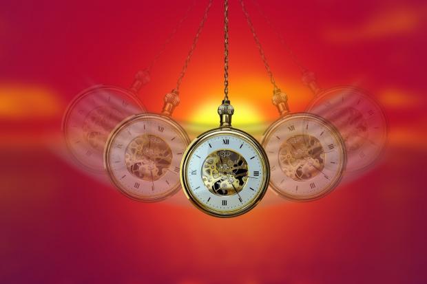 карманные часы на цепочке качаются на красном фоне