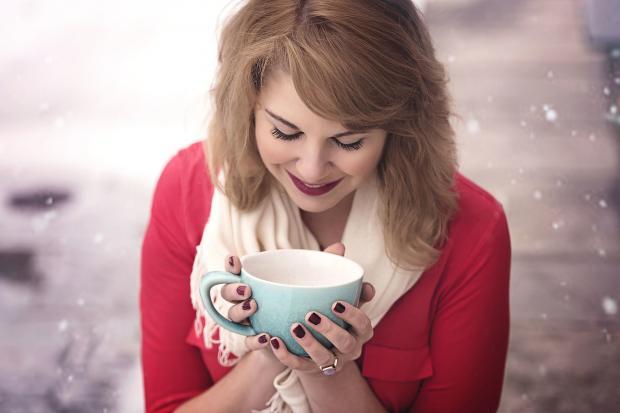 девушка в красном джемпере пьет кофе из голубой кружки