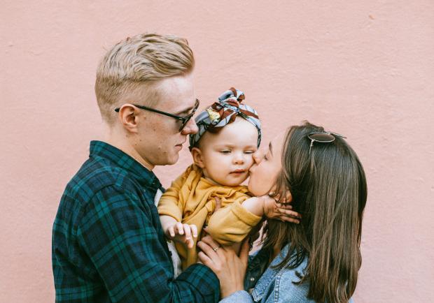 Молодые родители с маленьким ребенком на руках