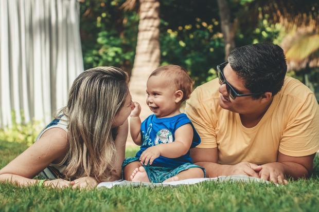 родители и маленький ребенок на траве в парке