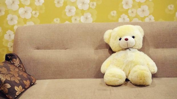 на песочном диване сидит желтый плюшевый медведь