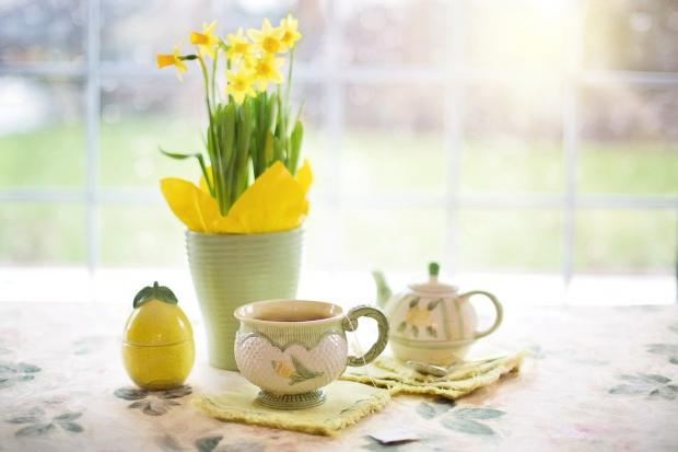 на чайном столе стоит ваза с желтыми нарциссами