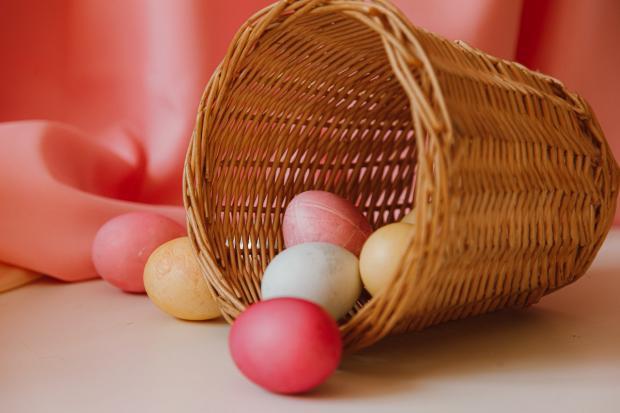плетеная корзинка с крашеными яйцами