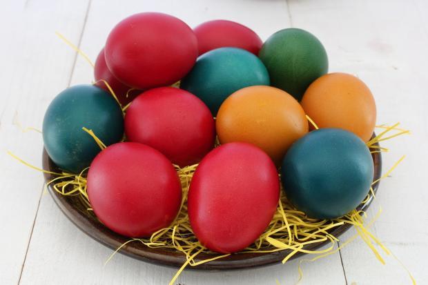 разноцветные крашеные яйца на тарелке лежат