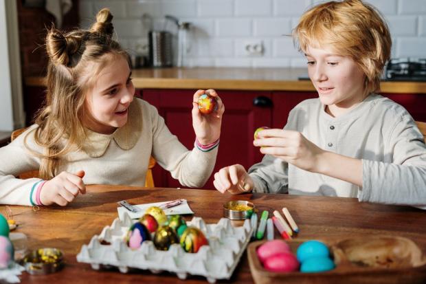 мама с дочкой раскрашивют яйца
