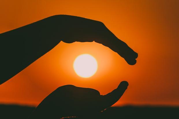 силуэта ладоней на фоне неба с солнцем