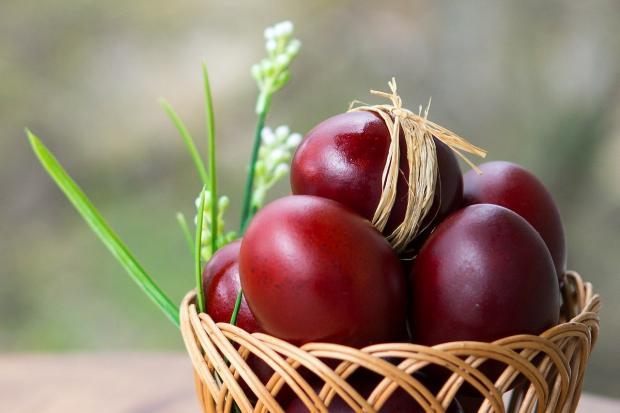 красные пасхальные яйца лежат в плетеной корзиночке