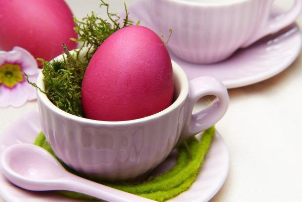 красное яйцо лежит в красивой белой чашке