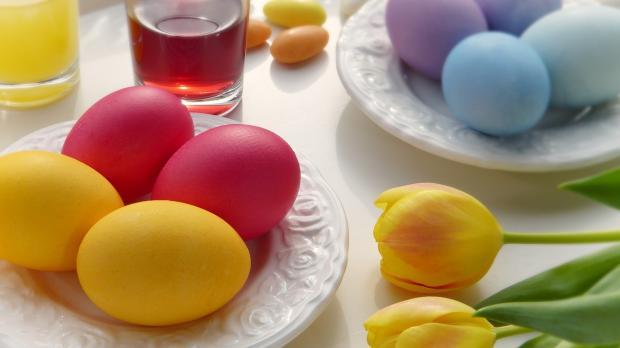 окрашенные пасхальные яйца лежат на тарелке рядом с желтыми тюльпанами