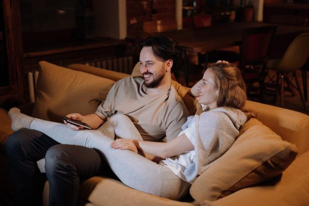на коричневом диване мужчина и девушка смотрят телевизор