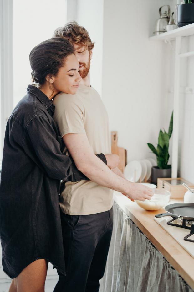 мужчина и девушка в черной рубашке вместе готовят на кухне