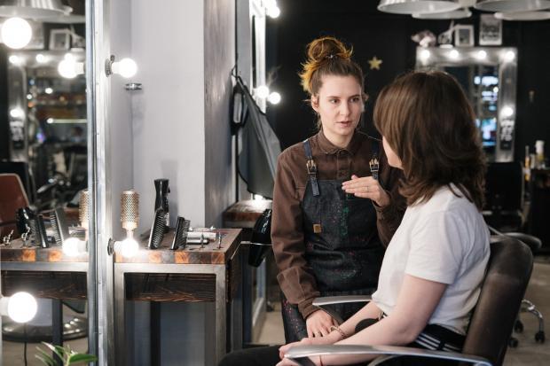 девушка в белой футболке разговаривает с парикмахером