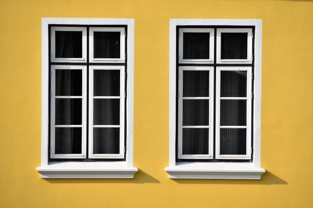 два белых окна на желтой стене