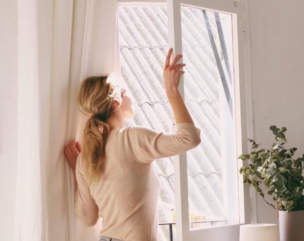 девушка в бежевой одежде возле окна
