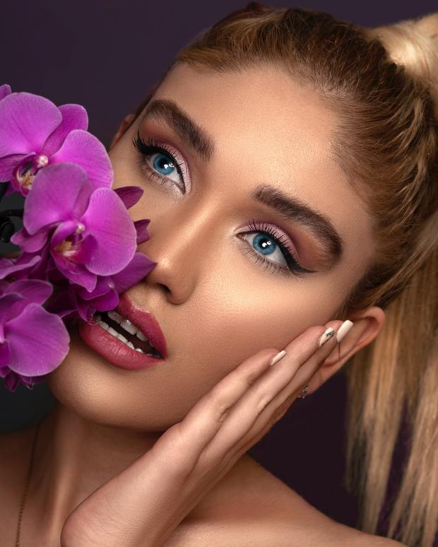 красивая девушка с сиреневыми цветами прижимает ладонь к щеке