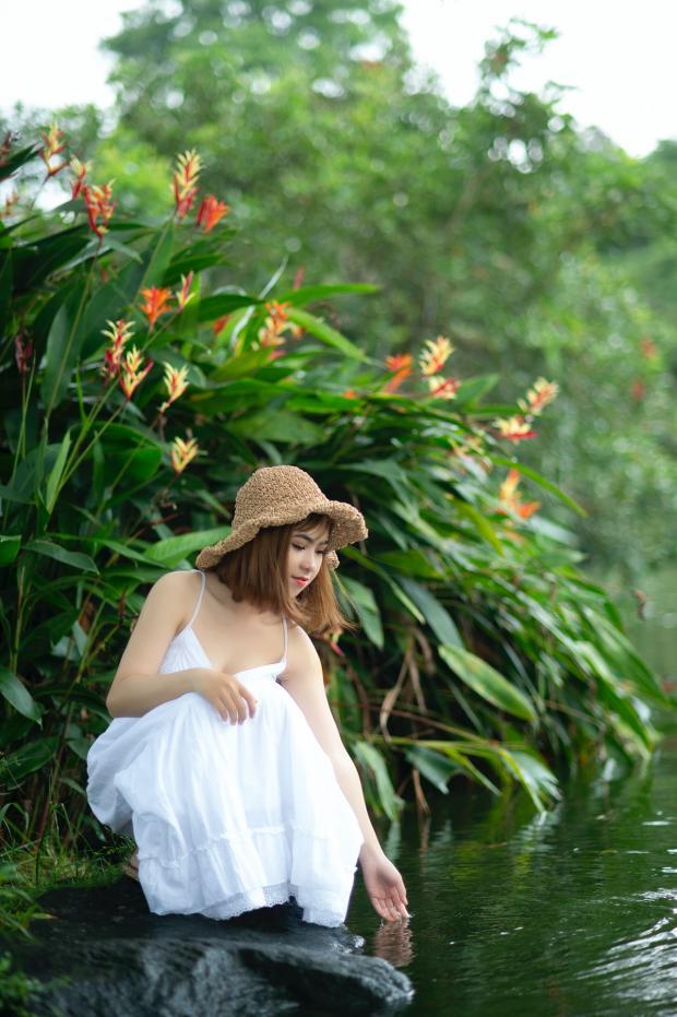 девушка в белом сарафане и соломенной шляпке склонилась к воде рядом с цветами