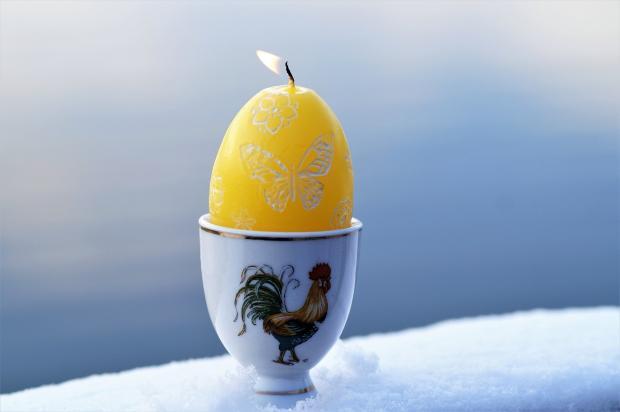 горит свеча в виде желтого яйца