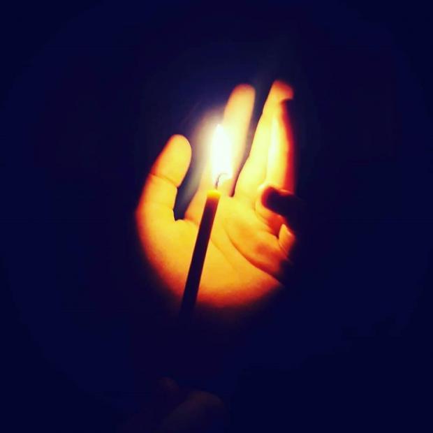 горящая свеча освещает ладонь человека