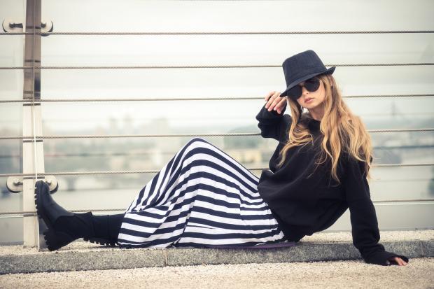 девушка в черно-белом костюме и шляпе сидит на мостовой