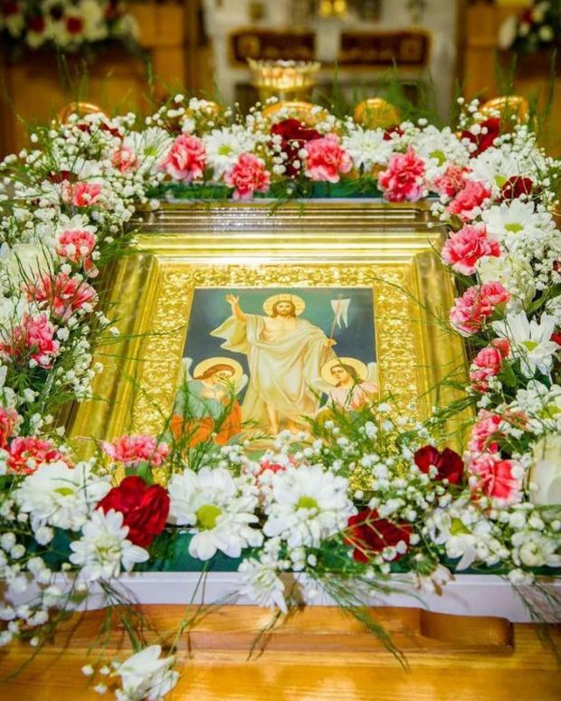 икона воскресения Христова лежит на аналое в окружении цветов