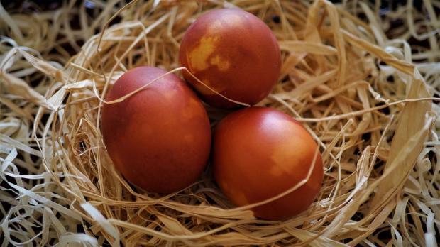 красные пасхальные яйца лежат в соломенном гнезде