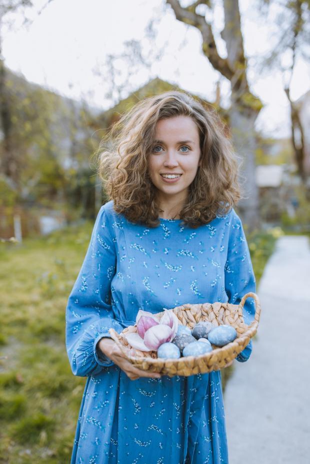 девушка держит плетеное блюдо с пасхальными яйцами